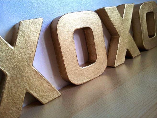Gold letter spelling XOXO