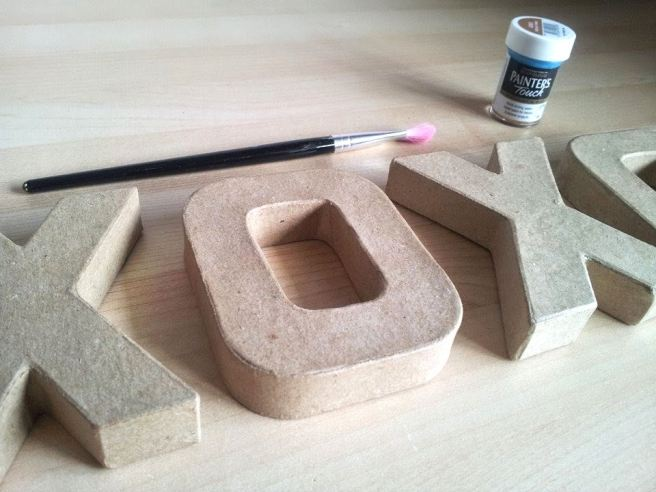 Cardboard letter, paint and paintbrush